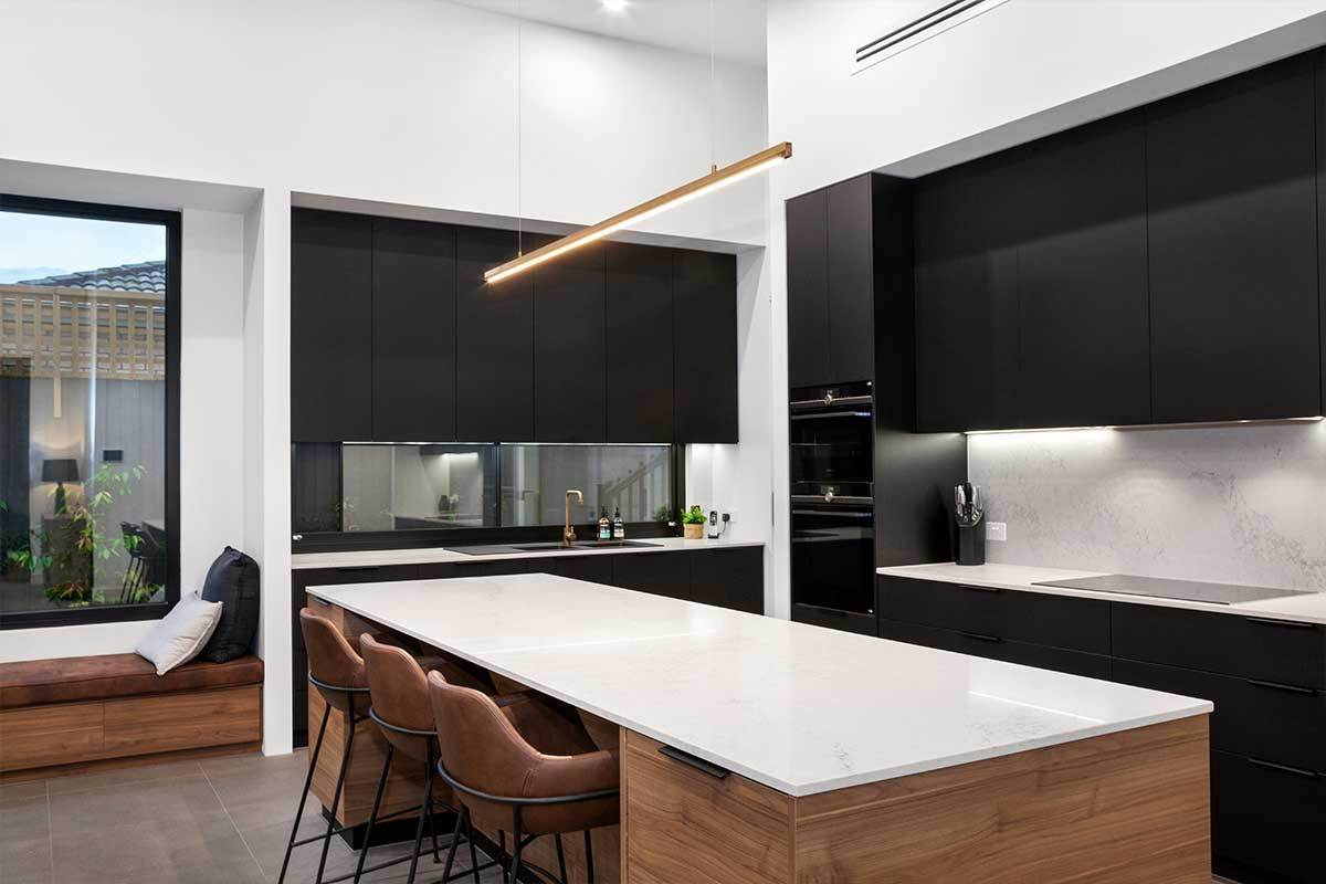 A kitchen with black cabinets and white benchtops